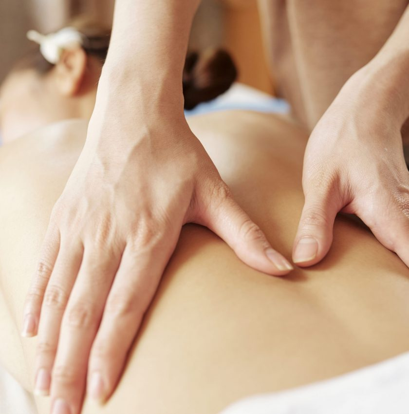 Hands of professional masseur massaging back of young female client